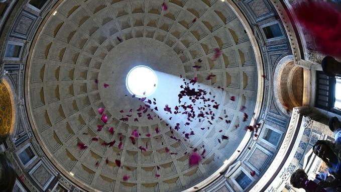 Rosenblätter-Regen am Pfingstsonntag, dem 8. Juni 2014 im Pantheon in Rom. Im Jahr 609, als Papst Bonifatius IV. die Pfingstmesse im Pantheon zelebrierte, soll bei seiner Predigt ein Rosenregen ?wie Feuerzungen? auf die Gläubigen niedergegangen sein. Daraus entstand der Brauch des pfingstlichen Rosenregens. Ein Regen aus roten Blütenblättern der ?Königin der Blumen? regnet auf die Köpfe der Gläubigen nieder.